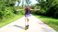Young woman rollerblading in park with arms in the air. video
