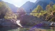 Young woman running across a suspension bridge over mountain stream video