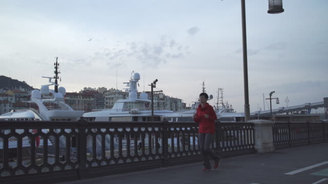 Young woman running in harbor in the morning video