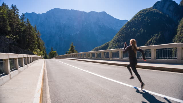 Young woman running in the middle of a road video
