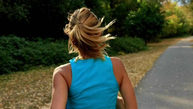 Young woman running in the park at sunset video