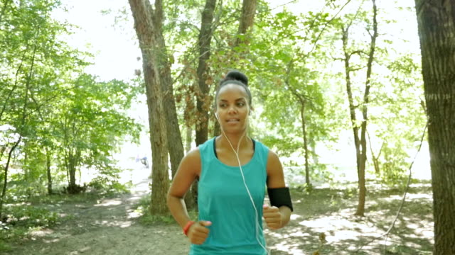 Young woman running off road on dirt path in wooded park video