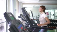 Young woman running on a treadmill in health club video
