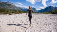 Young woman running on an empty river bed video