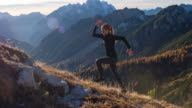 Young woman running up the mountain at sunset video