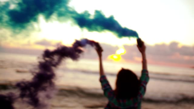 Young woman running with smoke bombs on beach at sunset video