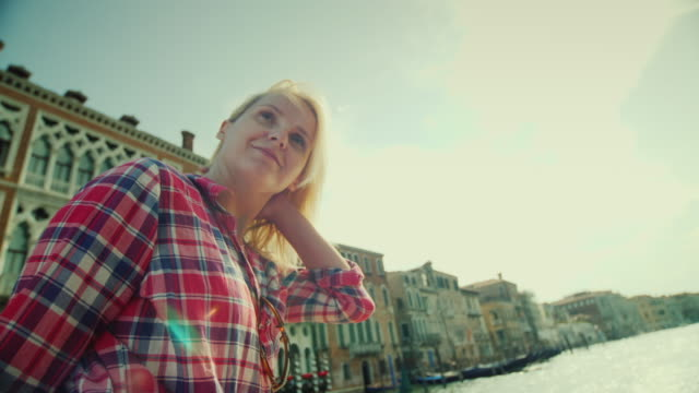 A young woman sails on a water taxi on the famous Grand Canal in Venice. Tourism in Italy video