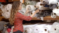 Young woman selecting fabric from rolls on storage shelves video