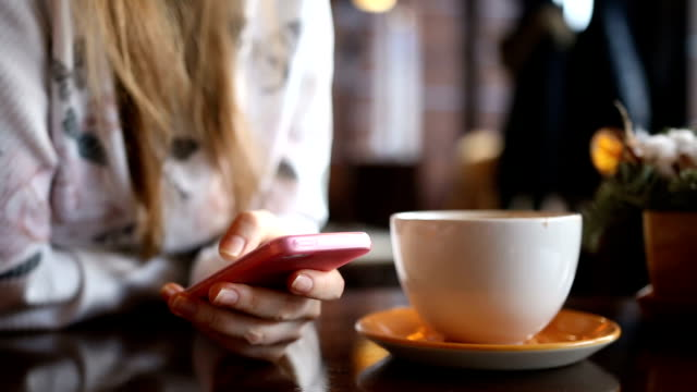 Young woman sending email via phone in cafe video