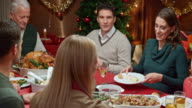 Young woman serving mashed potatoes to other family members at Christmas dinner video