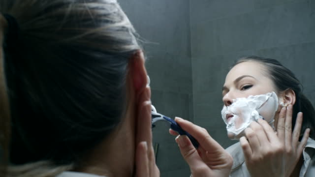 Young woman shaving her face video