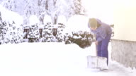Young woman shoveling snow near the house after intense snowfall video
