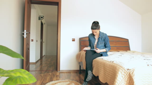 Young woman siting on the bed using digital tablet. video