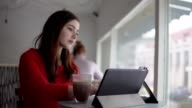 Young woman sits at a table at a restaurant using a tablet with access to the Internet, checking the mail and drinking coffee. video