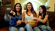 Young woman sits with mother and preteen sister to watch movie and eat popcorn video