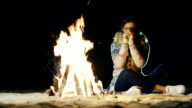 A young woman sitting alone by the fire, drinking tea, looking at the fire video