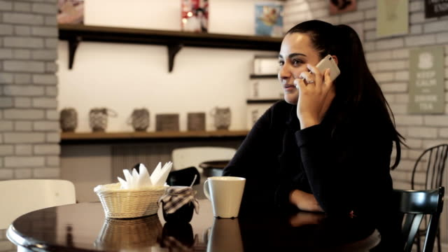 Young woman sitting at a table in a cafe and talking on the mobile phone. video