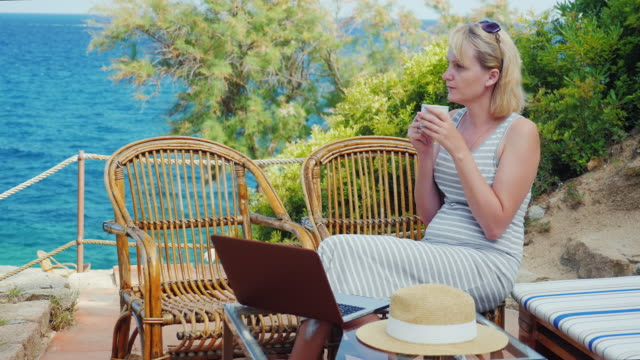 Young woman sitting at the table with a laptop in front of sea view. Lady freelancer working at the beach video