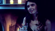 CU Young woman sitting by fireplace and holding champagne flute video