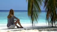 Young woman sitting by the ocean under a palm tree. video