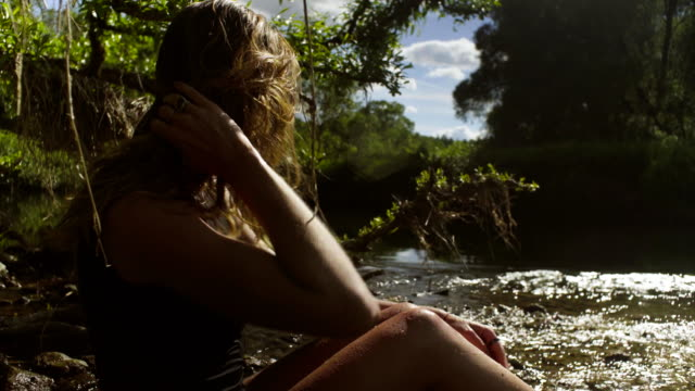 Young woman sitting in a river in shallow water video
