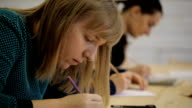 Young woman sitting in a row with others on classroom for drawing video