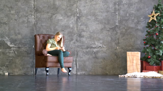 young woman sitting in an armchair and looking at the phone video