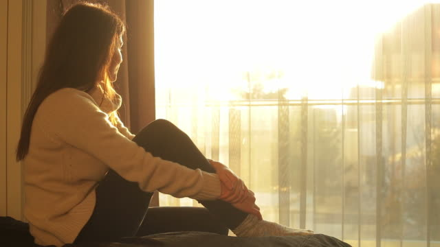 Young woman sitting in bed admiring the sunlight. video