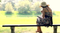 Young woman sitting in park with a diary video