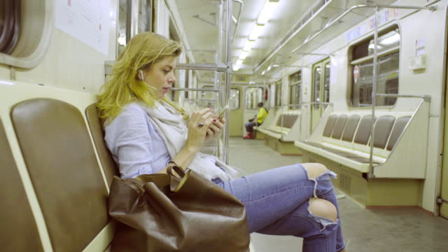 Young woman sitting in subway train video