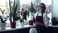 Young woman sitting near window with flowers video