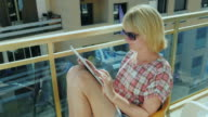 Young woman sitting on a chair balcony, enjoys a tablet video