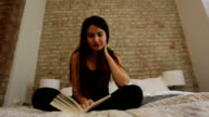 Young Woman Sitting on her Bed Reading video