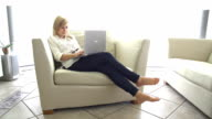 Young woman sitting on sofa, using laptop video