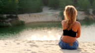 Young woman sitting on the beach, admiring the lake at sunset. View from the back video