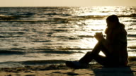 Young woman sitting on the beach on a cool windy day, drinking a hot drink from a cup. Keep warm in cold weather. On the Sunset video