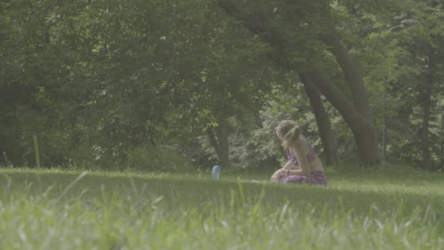 Young woman sitting on the grass in the park video