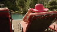 A young woman sitting poolside in the sun wearing a red hat, in slow motion video
