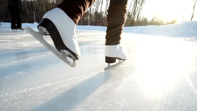 Young woman skating on ice with figure skates outdoors in the snow video