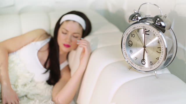 Young woman sleep with clock video