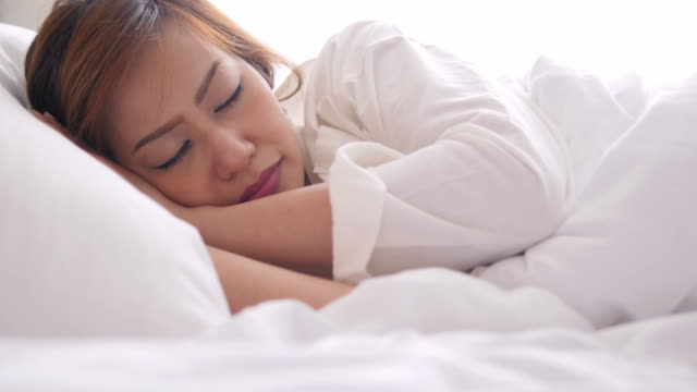 4K : Young woman sleeping in bed video