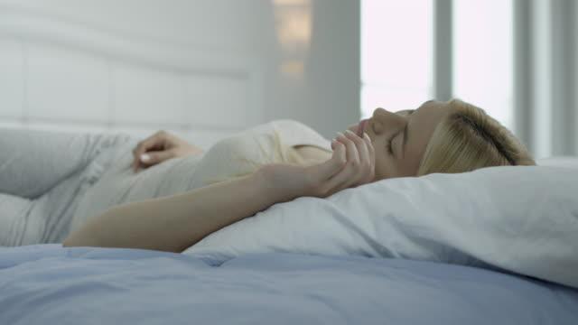 Young woman sleeping in bedroom video