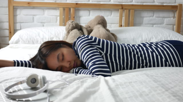Young woman sleeping on the bed with headphones video