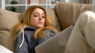 young woman sleeping with laptop on the sofa at home video