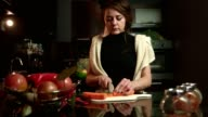 Young woman slicing cutting a carrot on the kitchen counter video