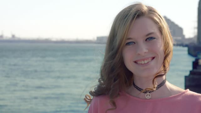 Young woman smiling at camera by water on pier video