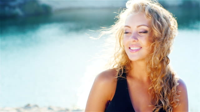 Young woman smiling into the camera, playing with her beautiful hair. On the beach portrait video