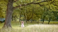 SLO MO DS A young woman smiling on a swing in the park video