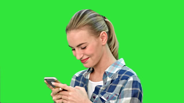 Young woman smiling while texting a message via cell phone on a Green Screen, Chroma Key video