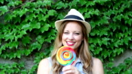 Young Woman Smiling With Lollipop With Ivy Background video
